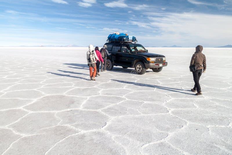 SALAR DE UYUNI BOLIWIA, KWIECIEŃ, - 17, 2015: Wycieczki turysycznej grupa z ich 4WD przy Salar De Uyuni soli mieszkaniem, Boliv obraz royalty free