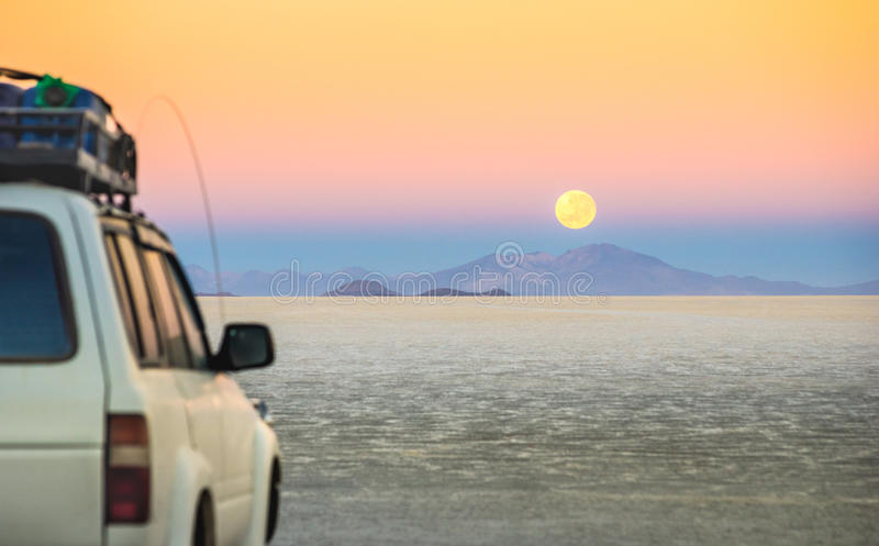 Salar De Uyuni at moon sunset - Adventure car trip in Bolivia. Full moon sunset with off road jeep vehicle on Salar De Uyuni - World famous nature wonder place stock photo