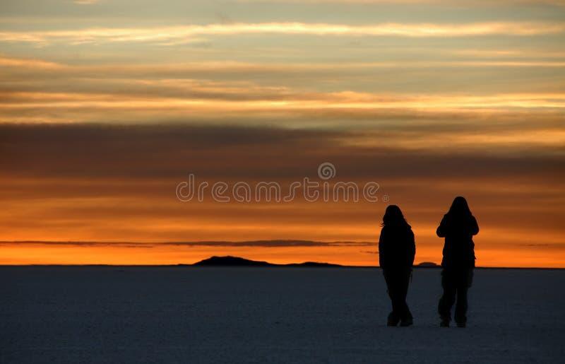 Salar at Sunrise. Two girls walking in the Salar Desert at sunrise. Salar De Uyuni, Bolivia royalty free stock photos