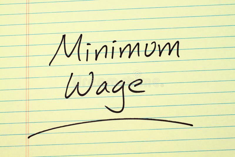Salario minimo su un blocco note giallo immagini stock