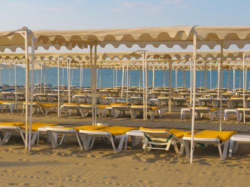 Salas brancas de plástico em praia vazia após estação quente foto de stock