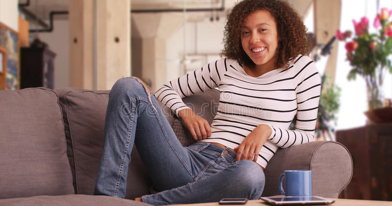 Salas de estar milenares da mulher negra em seu apartamento moderno imagem de stock royalty free