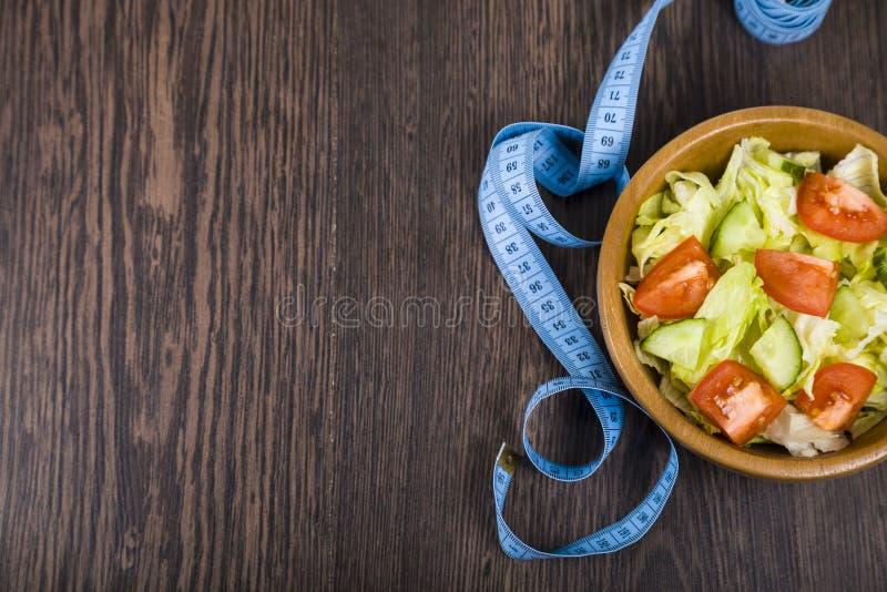 Salat in der hölzernen Schüssel und in messendem Band auf einer dunklen Tabellennahaufnahme stockbild