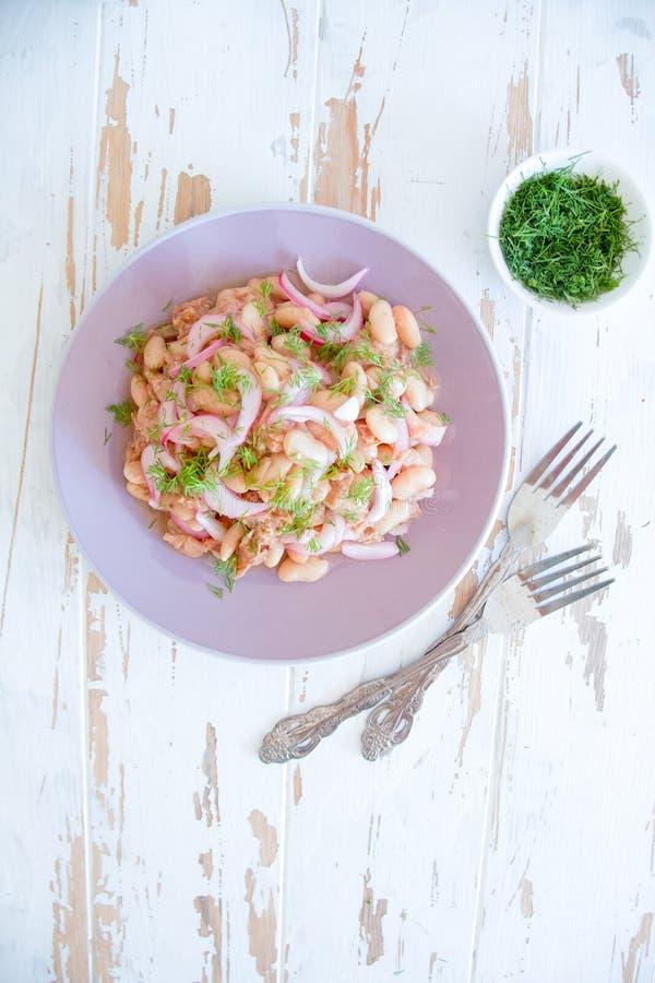Salat der weißen Bohne, des Thunfischs und der Zwiebel auf einer purpurroten Platte lizenzfreie stockfotos