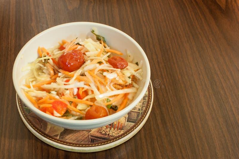 Salat des in Essig eingelegten Kohls mit Karotten und Kirschtomaten in der Salatschüssel auf hölzernem Hintergrund lizenzfreies stockbild