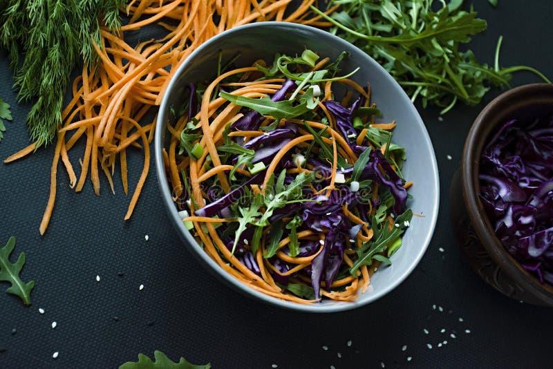 Salat des Rotkohls, der Karotten und der Grüns Verziert mit geschnittenem Gemüse und Kräutern Schnitt von Streifen Dunkler Hinter lizenzfreies stockbild
