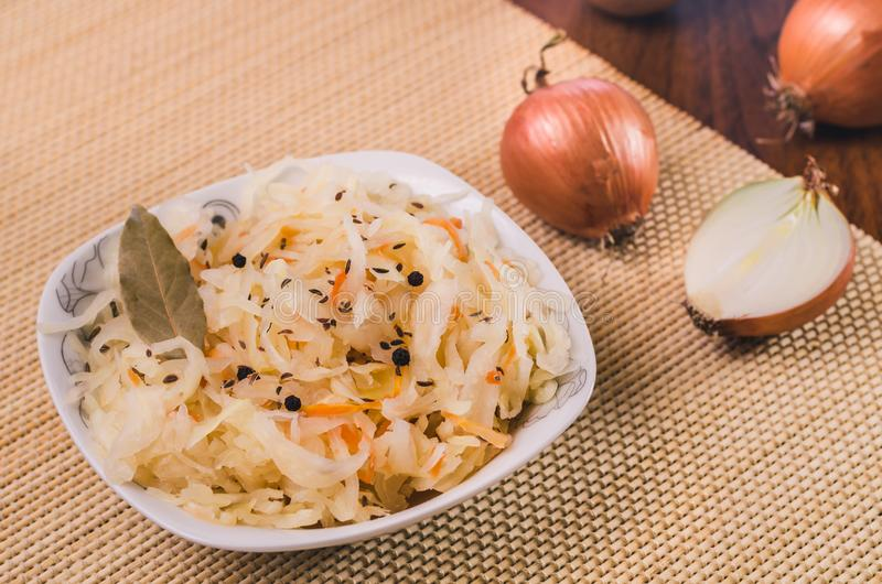 Salat des Sauerkrauts und der Karotten mit Lorbeerblättern, schwarzem Pfeffer und Kreuzkümmel in einer weißen Platte und in einig lizenzfreies stockfoto