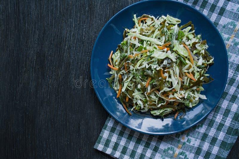 Salat des Weißkohls, des Meerkohls und der frischen Karotten würzte mit Olivenöl, Dill und Petersilie Dunkler h?lzerner Hintergru stockfotos