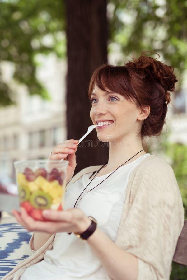 Salat junger Damen-Eating Fresh Fruit an der Bank stockfotografie