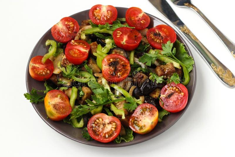 Salat mit Auberginen und Kirschtomaten auf einer dunklen Platte auf einem weißen Hintergrund, Draufsicht stockfotografie