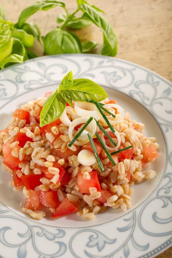 Salat mit buchstabiert und Tomaten lizenzfreies stockfoto