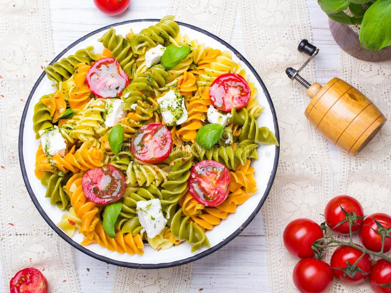 Salat mit bunten Teigwaren, Kirschtomaten, Feta und frischem Basilikum lizenzfreies stockfoto