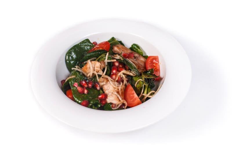 Salat mit Fleisch, Grüns, Granatapfel und Tomaten in einer Platte auf einem lokalisierten weißen Hintergrund stockbild