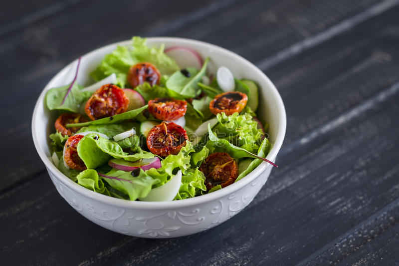 Salat mit Frischgemüse, Gartenkräutern und sonnengetrockneten Tomaten in einer weißen Schüssel stockfotos