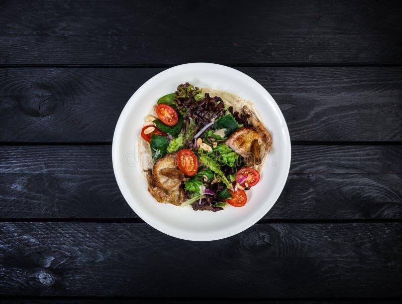 Salat mit gebratenen Wachteln mit Tomaten und Kopfsalat stockfotografie