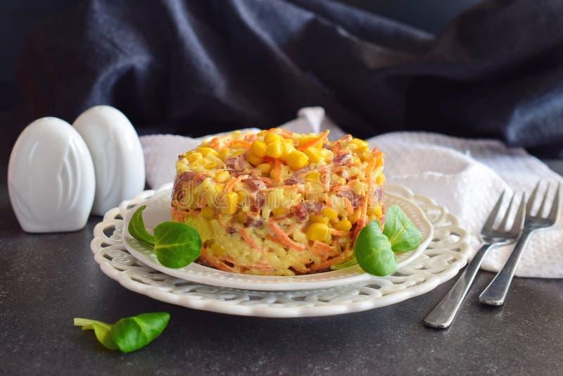 Salat mit geräucherter Wurst, Mais, Käse, frischer Karotte, Ei, Knoblauch und Jogurt auf einer weißen Platte auf einem abstrakten stockfotografie