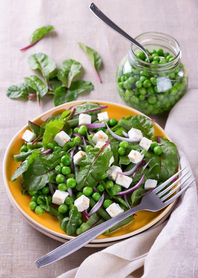 Salat mit grünen Erbsen, Bohnen, roter Zwiebel und Feta stockfotografie