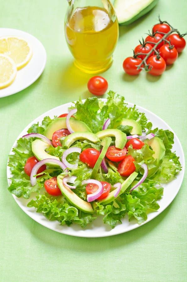 Salat mit letuce Blättern, Avocado, Kirschtomaten und Zwiebel stockbilder