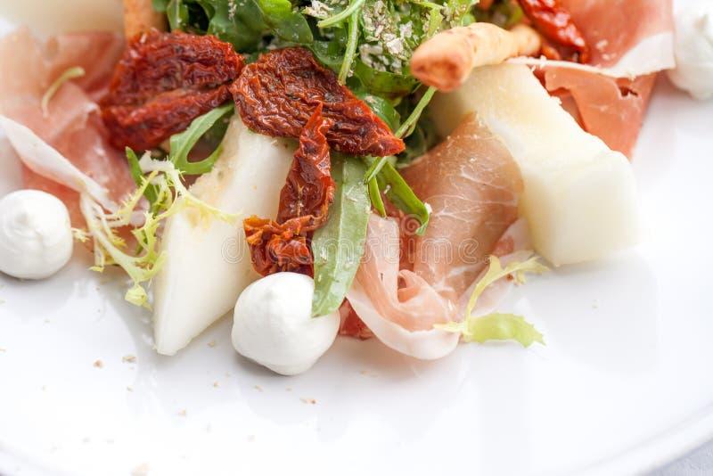 Salat mit Parmaschinken, Melonen und getrockneten Tomaten stockfotografie