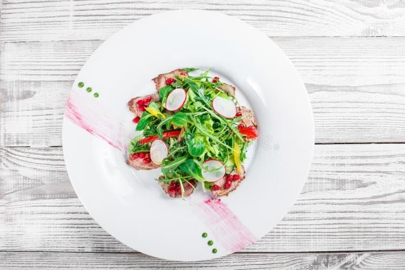 Salat mit Rindfleischsteak, Babyspinat, Kopfsalat, Gemüsepaprika und Körnern des Granatapfels auf hölzernem Hintergrundabschluß o stockbild