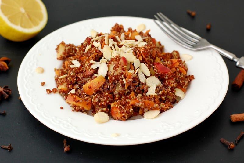Salat mit roter Quinoa, Apfel und Karotte mit Mandel auf weißer Platte auf schwarzem Hintergrund stockbild