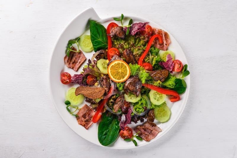 Salat mit Speck und der hühnerleber Auf einer hölzernen Oberfläche Beschneidungspfad eingeschlossen lizenzfreies stockbild