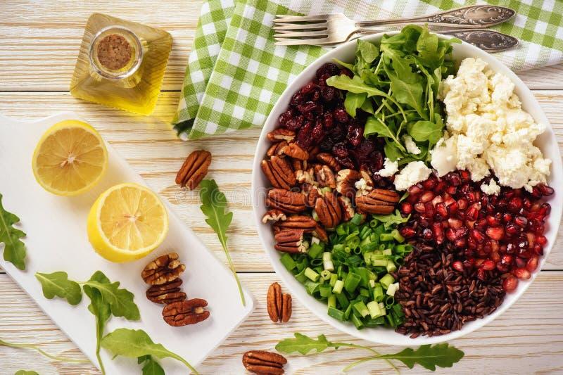 Salat mit Wildreisen, Arugula, Granatapfel, Pekannüssen, Moosbeeren und Feta stockbild