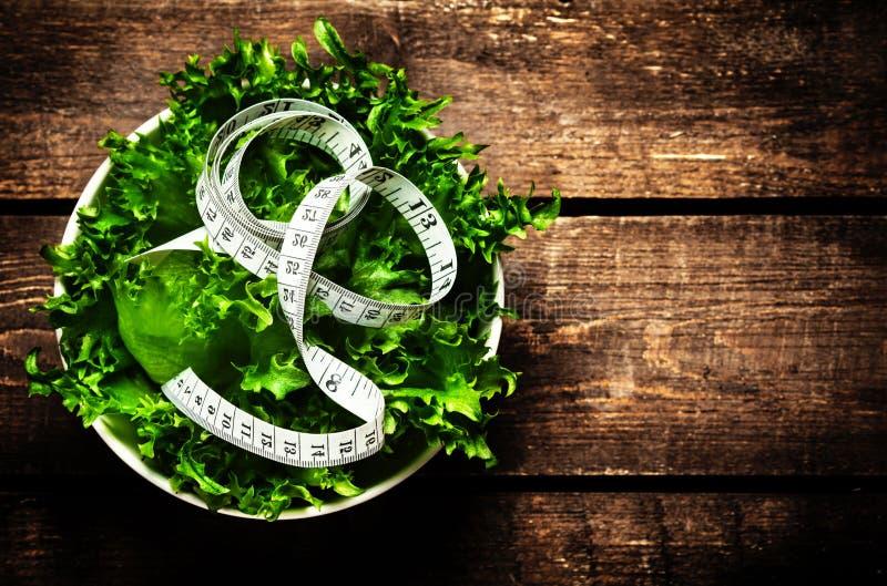 Salat und messendes Band auf rustikalem hölzernem Hintergrund Nähren Sie Nahrung stockfotografie