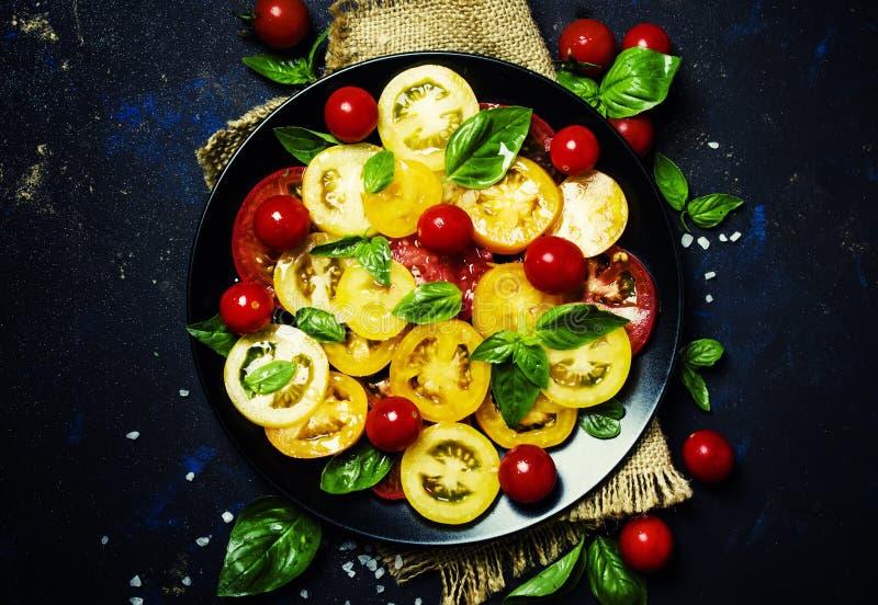 Salat von den bunten Tomaten, grüner Basilikum, zurückhaltende, Draufsicht lizenzfreie stockfotografie