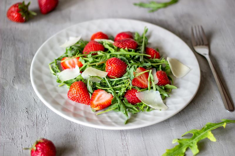 Salat von Erdbeeren, von Arugula und von K?se auf einem grauen Hintergrund diet?tische Lebensmittel lizenzfreie stockbilder