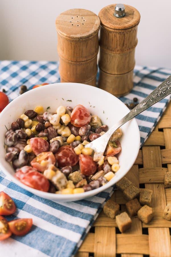 Salat von roten Bohnen, gelber Mais, Cracker Picknickkorb und ein schönes blaues Tuch stockbild