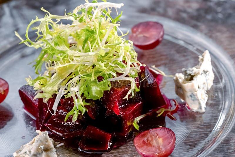 Salatnahaufnahme der feinschmeckerischen roten Rübe und des Blauschimmelkäses mit Arugula- und Kirschtomaten auf Glasteller stockfotografie