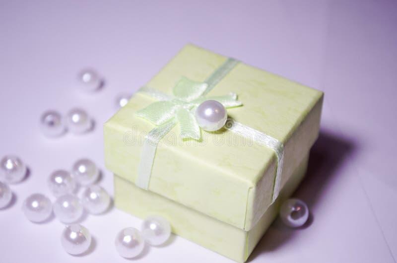 Salatne ask med en pärla Pärla på asken Plast- pärla Placerpärlor beads white royaltyfri fotografi