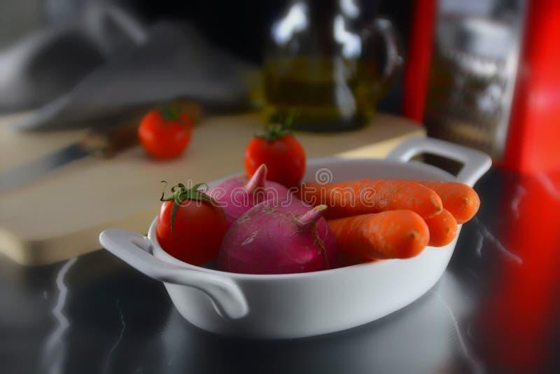 Salatzutaten in weißer Tasse Tomaten/Paradeiser, rote Radieschen und Karotten stockbilder