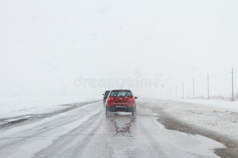 Salavat, Rússia - 26 de fevereiro de 2017: estrada com os carros no blizzard, condução perigosa na primavera imagem de stock