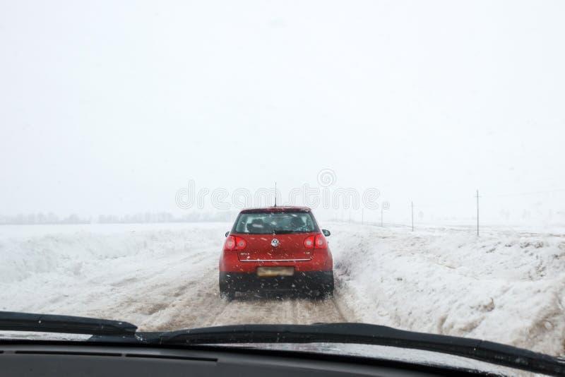 Salavat, Rusia - 26 de febrero de 2017: camino con el coche en la ventisca, conducción peligrosa en invierno fotografía de archivo