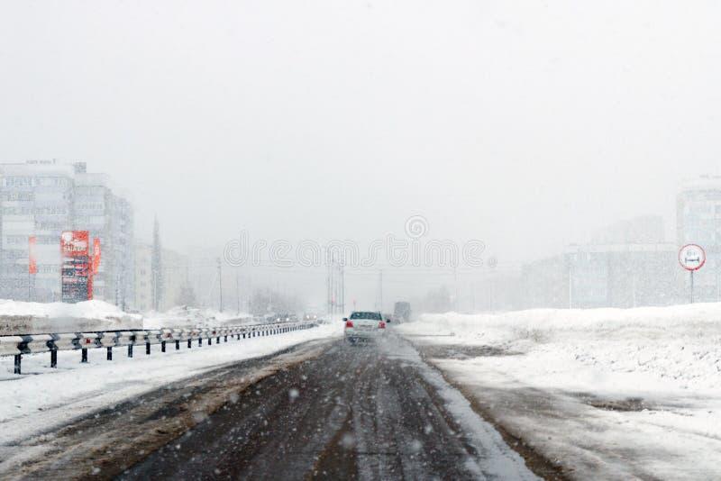 Salavat, Russia - 26 febbraio 2017: azionamento pericoloso nella bufera di neve, strada principale con le automobili nella bufera immagini stock libere da diritti