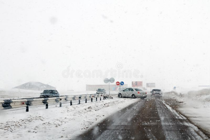 Salavat, Russia - February 26, 2017: highway with cars in blizzard, dangerous driving in snowstorm royalty free stock photo