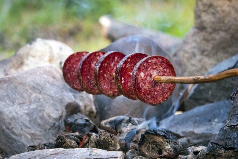 Salchicha ahumada de la carne asada sobre el fuego Salchichas rebanadas Salchicha empalada en un palillo Cena rápida que acampa e fotos de archivo libres de regalías