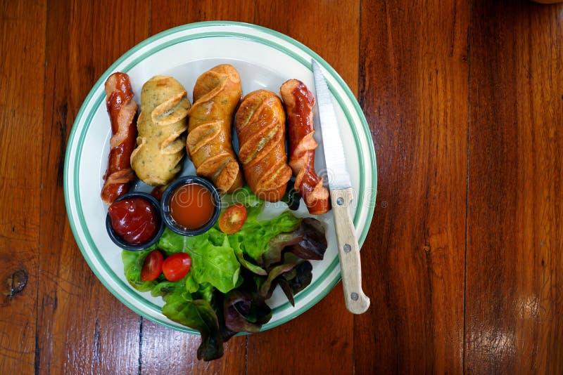 Salchicha asada a la parrilla con la verdura, la taza de salsa de tomate y la salsa de chile foto de archivo