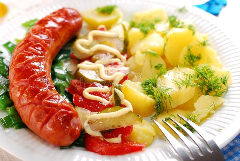 Salchicha asada a la parrilla, ensalada vegetal y patata fotografía de archivo libre de regalías