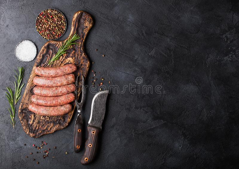 Salchicha cruda de la carne de vaca y de cerdo en la vieja tajadera con el cuchillo del vintage y bifurcación en fondo negro Sal  fotos de archivo