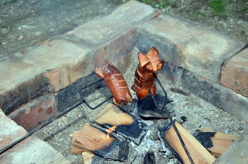 Salchicha de asado a la parilla dos sobre un fuego en chimenea del ladrillo imagen de archivo
