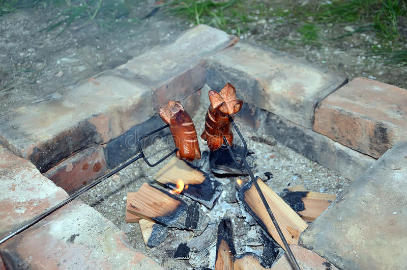 Salchicha de asado a la parilla dos sobre un fuego en verano imagen de archivo