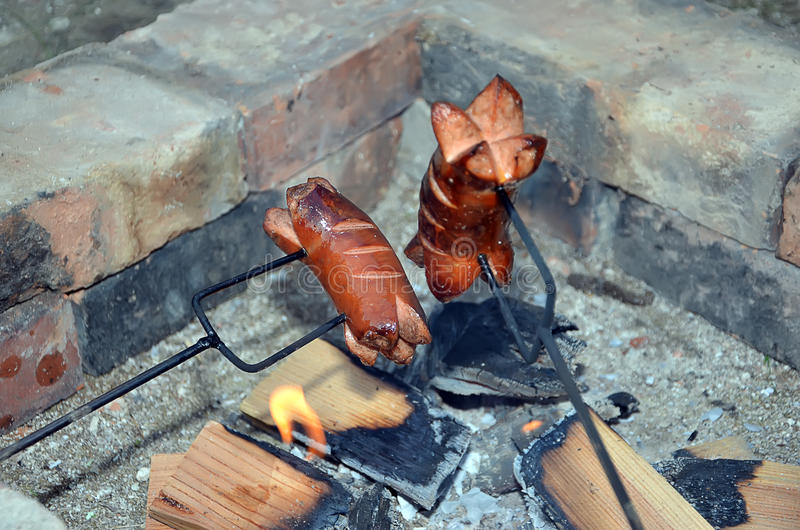 Salchicha de asado a la parilla dos sobre un fuego en verano foto de archivo libre de regalías