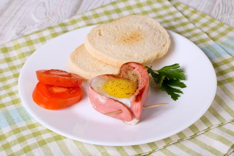 Salchicha en un huevo frito en forma de corazón foto de archivo