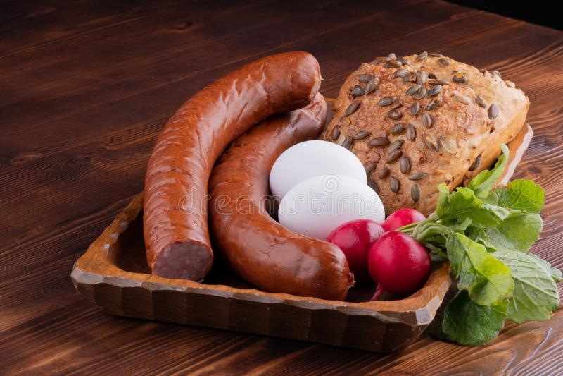salchicha fumada con el pan y el rábano, comida rústica en una tabla de madera foto de archivo