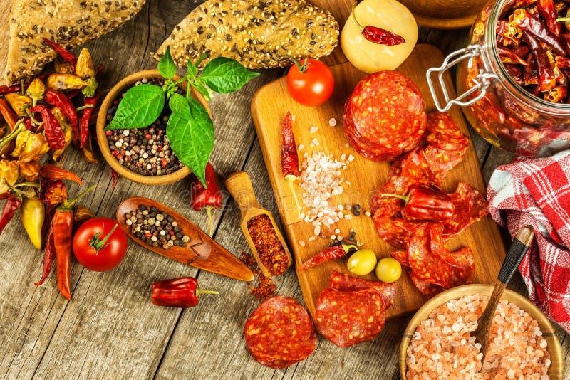 Salchicha o salami con pimienta de chile con las hierbas en la tabla de madera Salami picante con el chile Alimento gordo malsano foto de archivo