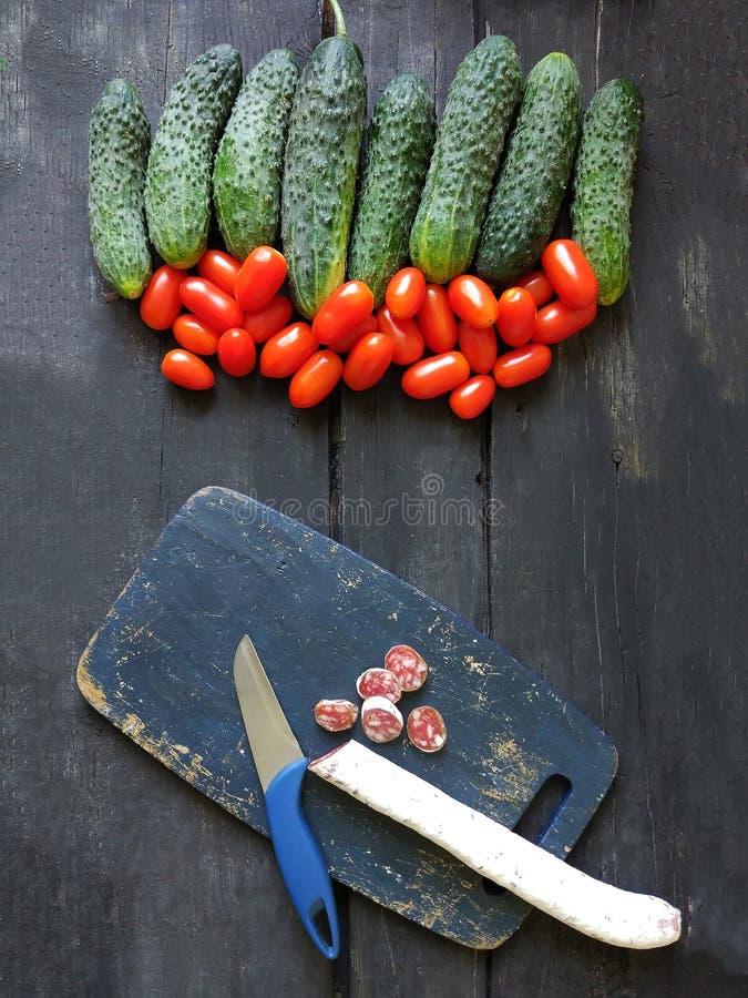 salchicha Seco-curada en el tablero oscuro, los tomates frescos y los ccumbers foto de archivo