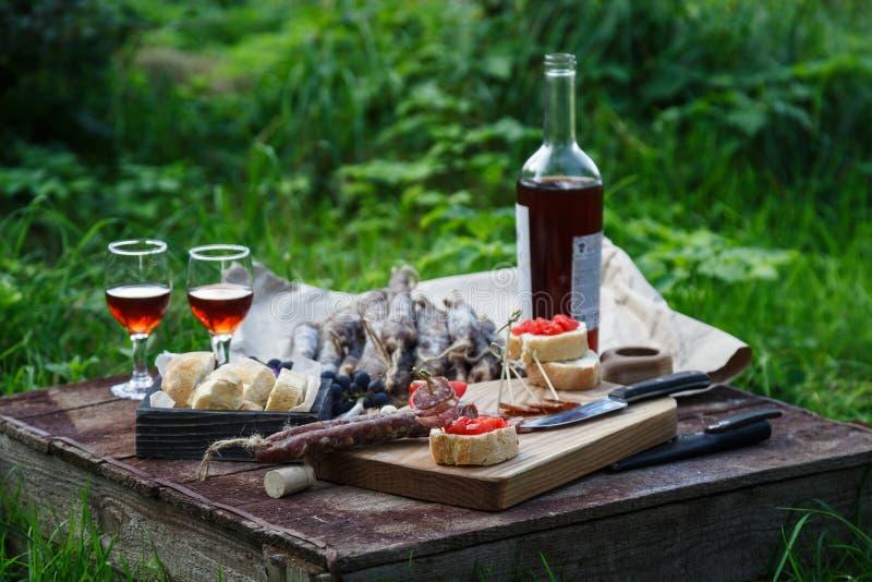 Salchicha, tomate, pan y vidrios de vino rojo, contryside imagenes de archivo